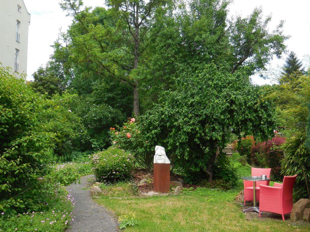 Blick in den hinteren Teil des Gartens mit Skulptur